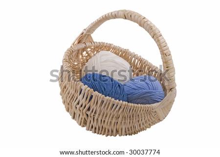 Three multi-coloured balls of yarn in wicker basket - stock photo