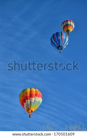 Three Multicolored and Striped Hot Air Balloons in the sky - stock photo
