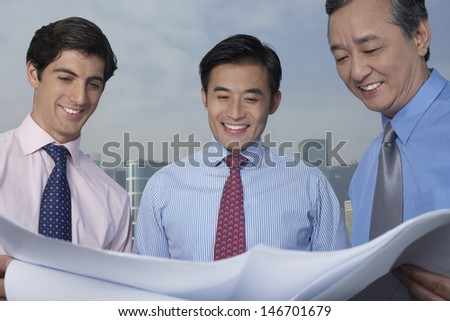Three multiethnic businessmen looking at blueprint with buildings in background - stock photo