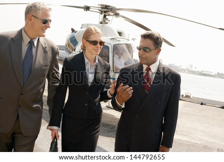 Three multiethnic businesspeople arriving from helicopter - stock photo