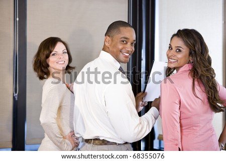 Three multiethnic office workers reading report in boardroom, focus on couple on right - stock photo