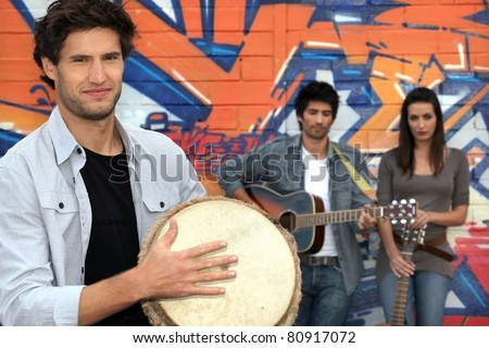 three musicians in front of a tagged wall - stock photo