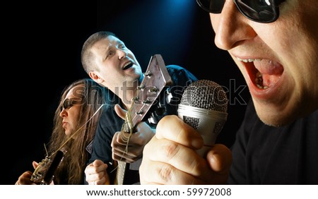 Three musicians sing a song close up - stock photo