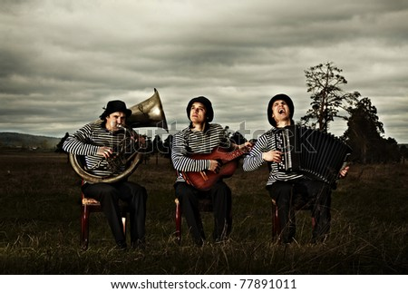 Three musicians sit and play on grass against sky - stock photo
