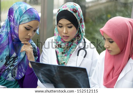 Three Muslim doctor discuss about xray result - stock photo