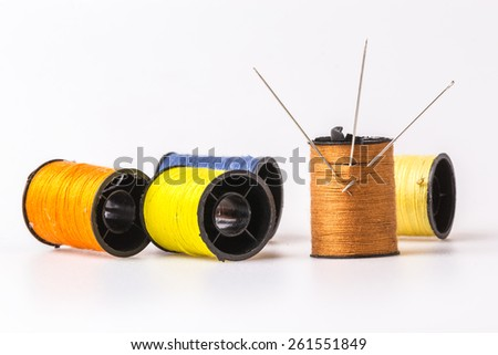 Three needle embroidery sewing thread rolls in brown. The winding down of various colors on a white background - stock photo