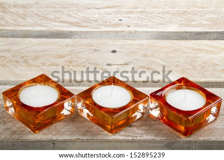 Three new candles in candle holders on wooden surface