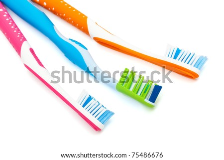 three new toothbrushes on a white background - stock photo