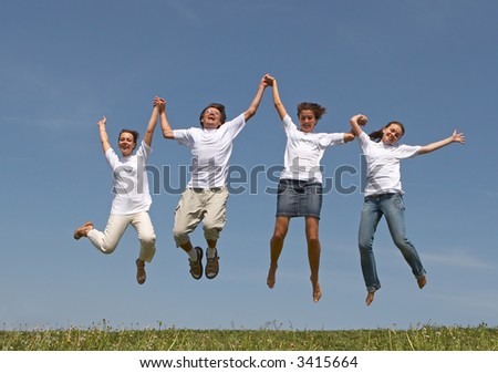 Three nice girls and young the man jump on a green grass on a background of the blue sky