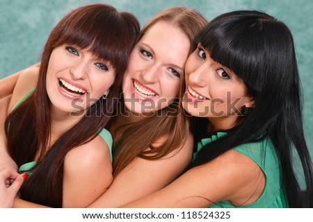 three nice girls in green dresses on a green - stock photo