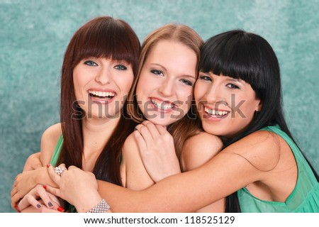 three nice girls in green dresses on a green background - stock photo