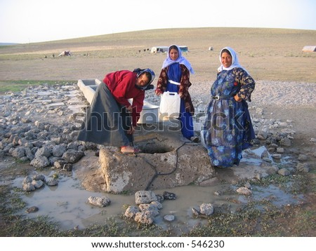 Three nomadic women getting water from a well - stock photo