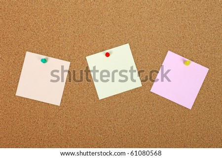 Three note papers attached to cork board with pins.