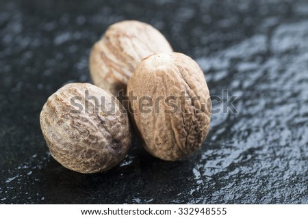Three Nutmegs on black stone background - stock photo