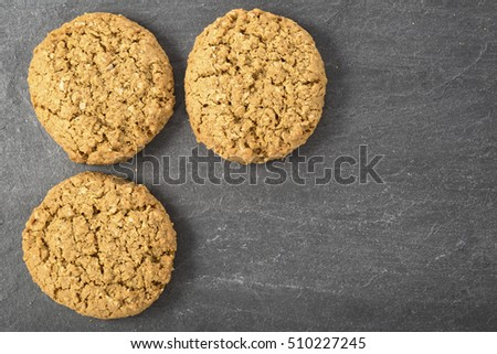 Three oatmeal cookies on a stone surface with copy space