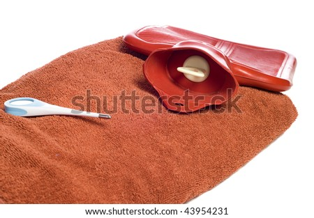 Three objects people commonly use when they are sick, including a hot water bottle, a thermometer, and a towel, isolated against a white background - stock photo