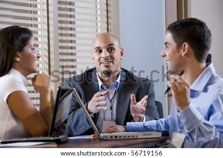 Three office colleagues having discussion at desk - stock photo