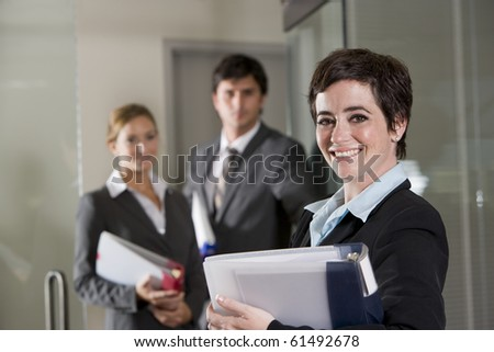 Three office workers at door of boardroom, focus on woman in foreground