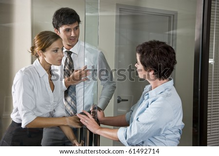 Three office workers at glass door of boardroom, one inside, two outside