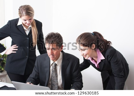 Three office workers gather around the computer in a discussion. Large blank wall behind, provides copy space