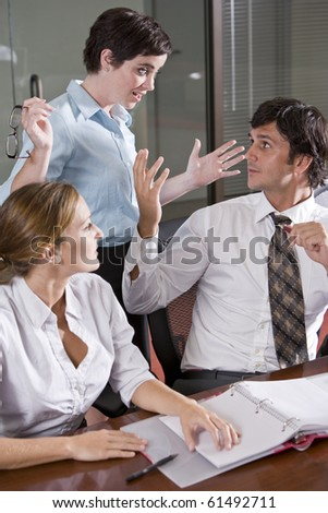 Three office workers in boardroom, having lively discussion - stock photo