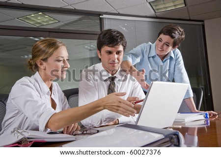 Three office workers in boardroom, working together on documents and laptop