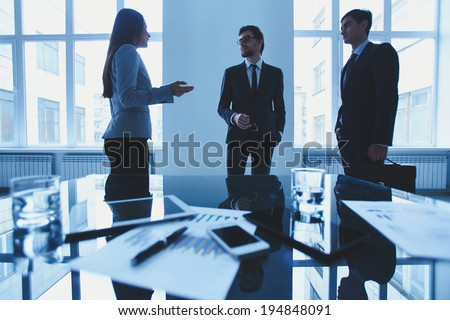 Three office workers interacting at meeting by workplace - stock photo