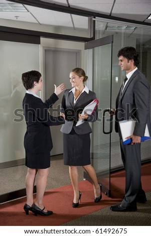 Three office workers shaking hands at door of boardroom