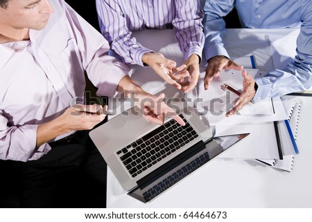 Three office workers working together on project, talking, gesturing and looking at laptop computer screen - stock photo
