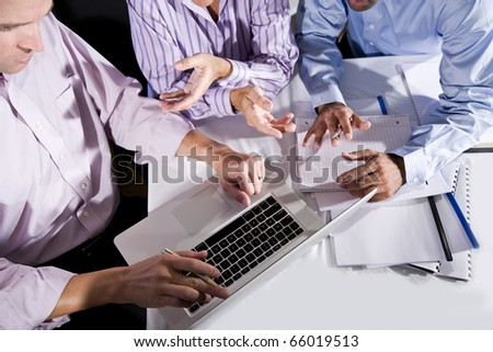 Three office workers working together on project, talking, gesturing and looking at laptop computer screen