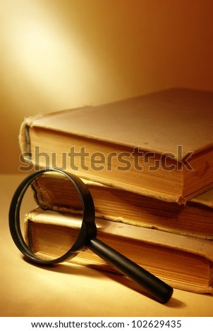 three old books and magnifying glass - stock photo