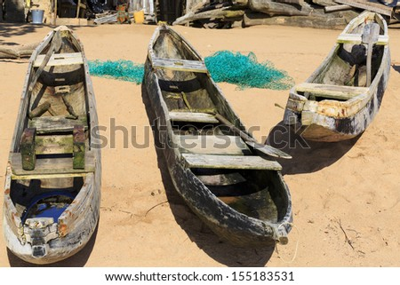 Three old dugout canoes on the beach with nets in Axim, Ghana - stock photo