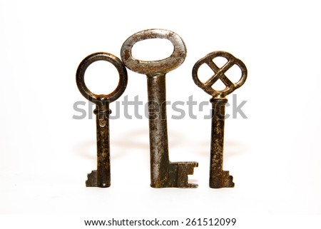 Three old keys to the safe on a white background
