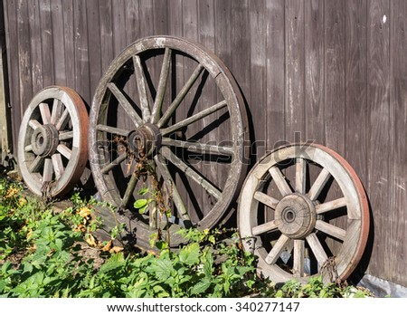 Good Three Old Wagon Wheels With Metal Rims Leaning Against A Wall Of Wooden  Planks