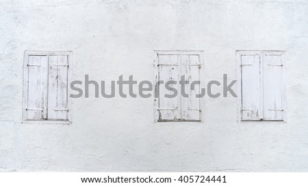 Three old windows with closed window shutters in a bright facade  - stock photo