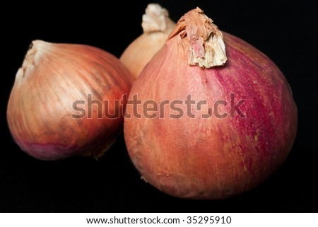 Three onions isolated on black background