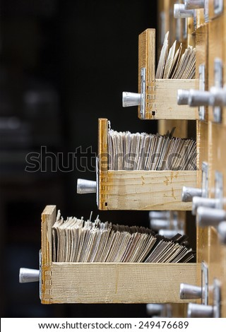 Three open drawers in the archive library on a dark background - stock photo