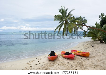 Three orange kayaks sit on a resort beach on an exotic island in Fiji. - stock photo