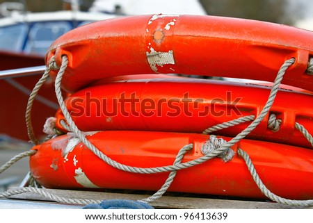 three orange life rings piled on top of each other onboard a boat on the river thames - stock photo