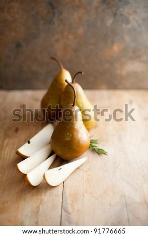 Three Organic Bosc Pears on Old Cutting Board - stock photo