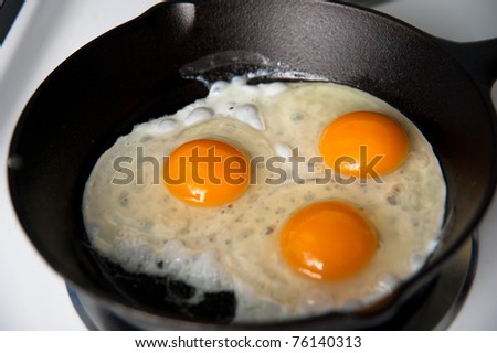 Three Organic Chicken Eggs Being Fried on Cast Iron Skillet