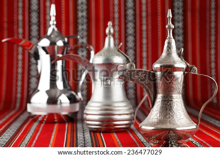 Three ornate Dallah are placed on traditional red fabric from the Middle East. Dallah is a metal pot for making tea and coffee  - stock photo