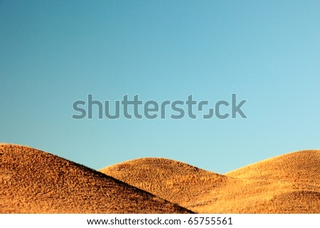 Three overlapping hills against a clear steel blue sky. - stock photo