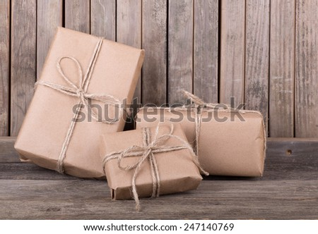Three packages wrapped in brown paper and string on old wood deck - stock photo
