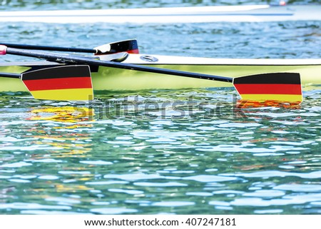 Three paddles with german coat of arms label dive into the water - stock photo