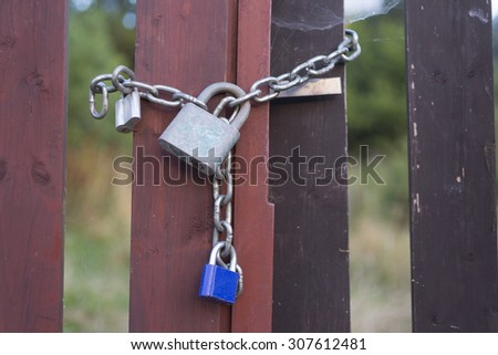 Three padlocks on an iron chain