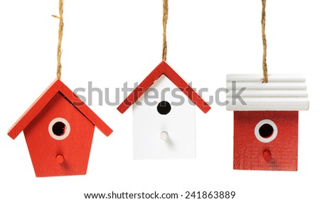 Three painted birdhouses hanging on white background - stock photo