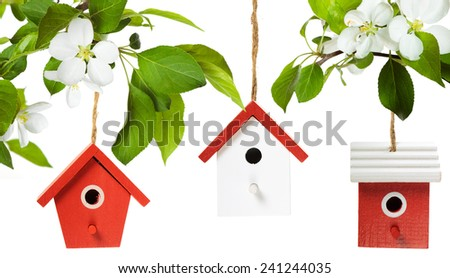 Three painted birdhouses with apple blossom on white background - stock photo