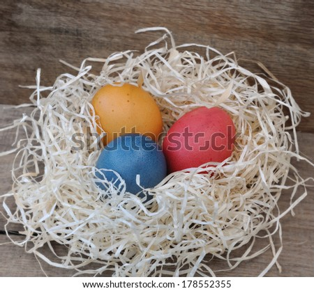 three painted eggs in straw on wooden board