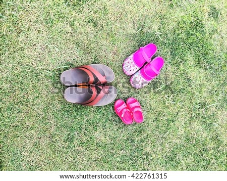 three pair of shoes in father big, mother medium and son or daughter small kid size in grass park - stock photo